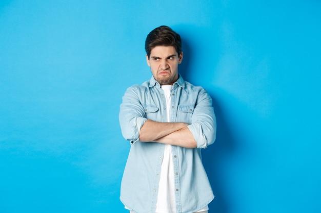 怒っている男は胸に腕を組んで侮辱的な表情で目をそらし、青い背景に腹を立てて立っている