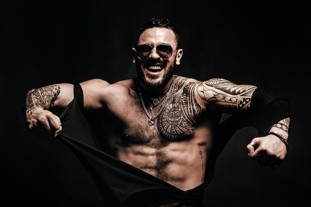 Angry guy fashion brutal guy with sexy body ripped shirt sexy man with muscular body and bare torso
