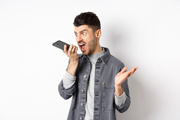 Злой парень кричит на громкую связь, кричит на мобильный телефон, оставляя сердитое голосовое сообщение, стоя на белом фоне.