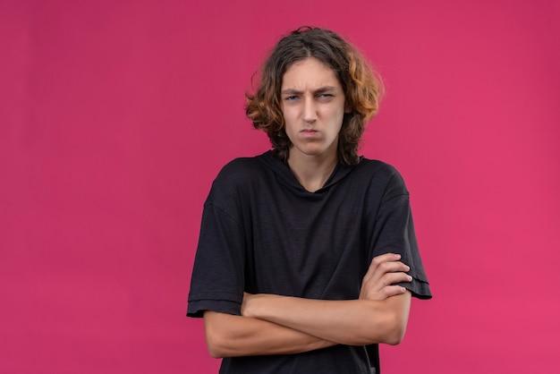 ピンクの壁に手を交差させる黒いtシャツの長い髪の怒っている男