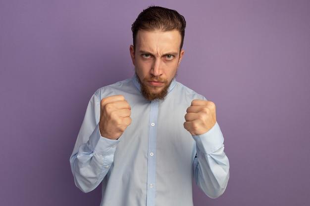 L'uomo biondo bello arrabbiato tiene i pugni isolati sulla parete viola