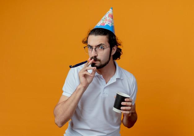 笛を吹いて、オレンジ色の背景で隔離のコーヒーのカップを保持している誕生日キャップの怒っているハンサムな男
