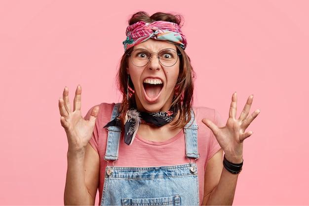 Злая женщина-хиппи раздраженно кричит и жестикулирует, у нее нервное выражение лица, она получает плохие новости, стоит над розовой стеной и терпит
