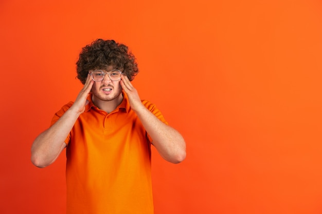 Angry holding head, wtf. caucasian young man's monochrome portrait on orange  wall. beautiful male curly model in casual style.