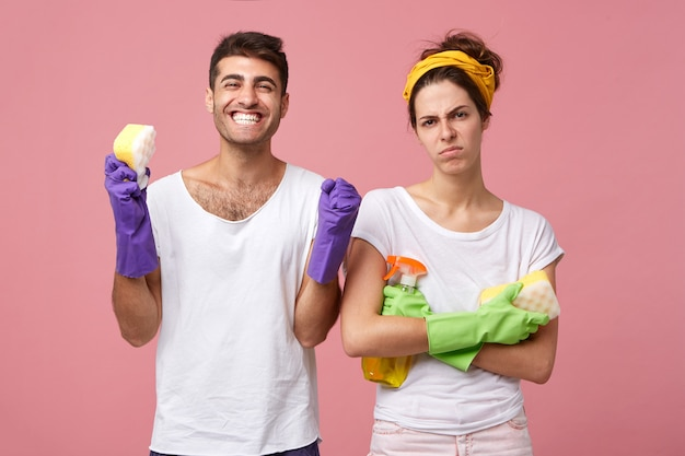 Angry housewife standing crossed hands holding sponge with detergent standing near her happy husband who is rejoicing finishing his work. couple going to do spring cleaning in their house isolated