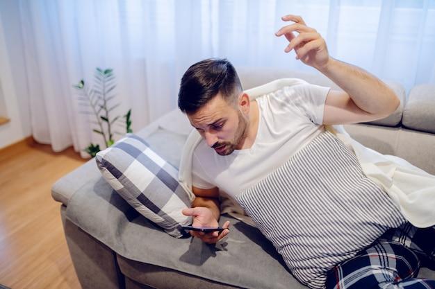 怒っている病気の白人男性が誰かの電話に邪魔される。