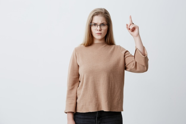 Angry and indignant young caucasian female with blonde hair and eyeglasses looking up and pointing index finger upwards, feeling irritated with noise coming from neighbors above. body language
