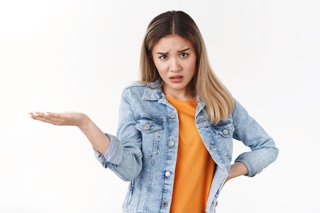 화가 난 격렬한 불만을 품은 아시아 금발 소녀가 짜증을 내며 이마 아래에서 혼란스러운 제품 손을 바라보고 불만을 품은 응시가 질문을 받았습니다.