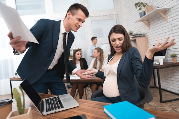 Angry irate boss yelling at pregnant employee