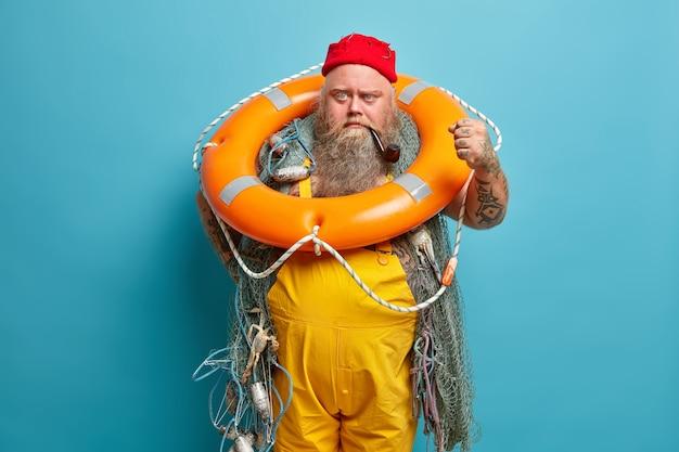 怒っているイライラした船乗りは拳を握りしめ、膨らんだリングでポーズをとり、赤い帽子と黄色のオーバーオールを着て、忙しい釣りをします