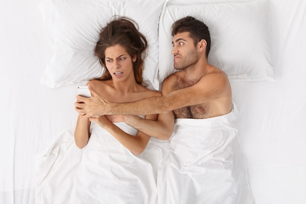Злой, раздраженный взрослый мужчина отнимает у женщины мобильный телефон, требует внимания и живого общения, раздраженный женской технологической зависимостью, остается в постели перед сном. выстрел сверху.
