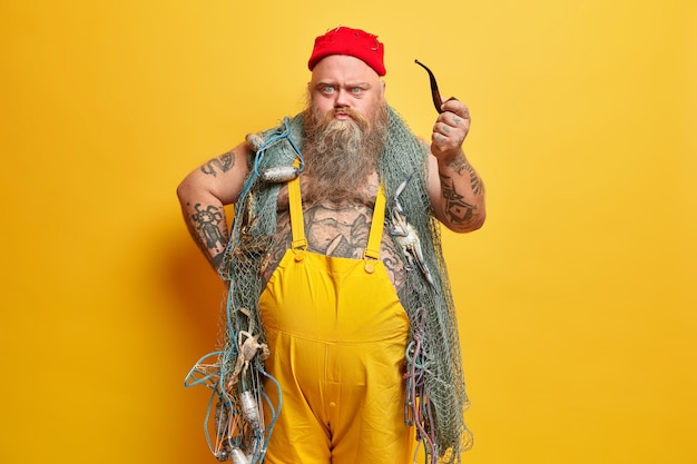 Angry irritated bearded boatswain looks with sullen expression directly at you holds smoking pipe dressed in overalls has fishing net around neck