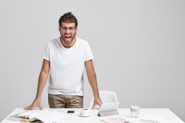 アイウェア叫びで怒っているイライラしたひげを生やした男性従業員は彼の気性を失っています