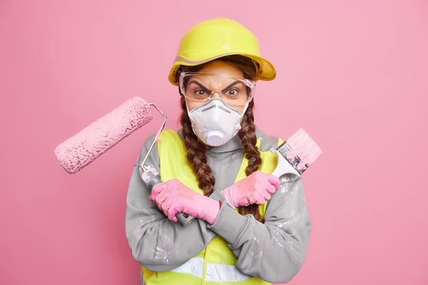 화가 난 여성 건축업자는 집 리모델링과 관련된 수동 작업을 위해 준비된 수리 도구를 들고 팔짱을 끼고 있습니다.