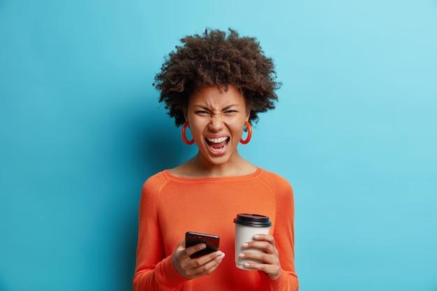 화난 초조 한 여자는 휴대 전화를 사용하여 큰 소리로 얼굴을 웃으며 커피를 마시고 파란색 벽에 고립 된 주황색 점퍼를 착용하고 휴대 전화에서 이상한 것을 본 후 찡그린 다