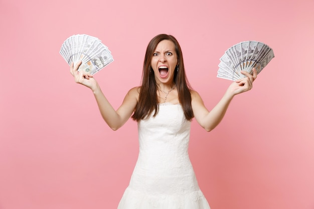 Angry irritated woman in white dress screaming, holding bundle lots of dollars, cash money