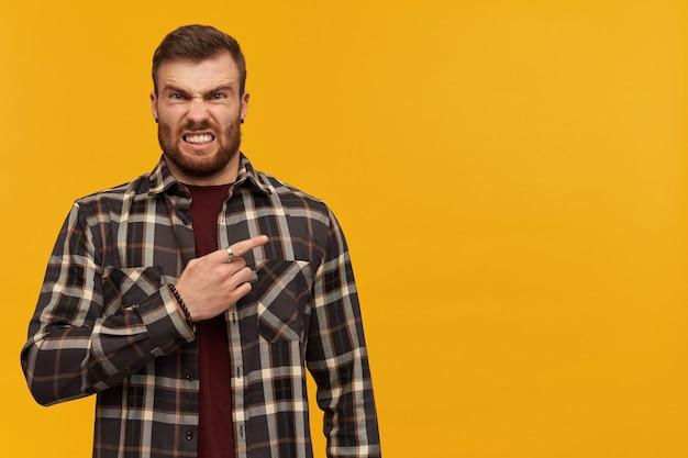 Giovane arrabbiato irritato in camicia a quadri con la barba in piedi e indicando con il dito di lato sopra il muro giallo
