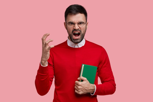 Angry irritated young teacher gestures with hand in annoyance, dressed in red jumper, carries textbook, yells at pupils