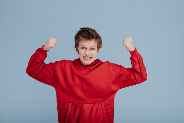 Злой ребенок мальчик в красной толстовке с поднятыми руками изолирован на синем фоне копией пространства