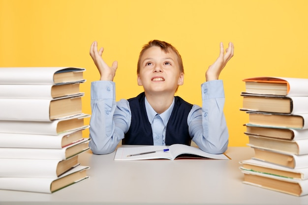 Angry kid sitting in the classroom with a lot of books isolated.
