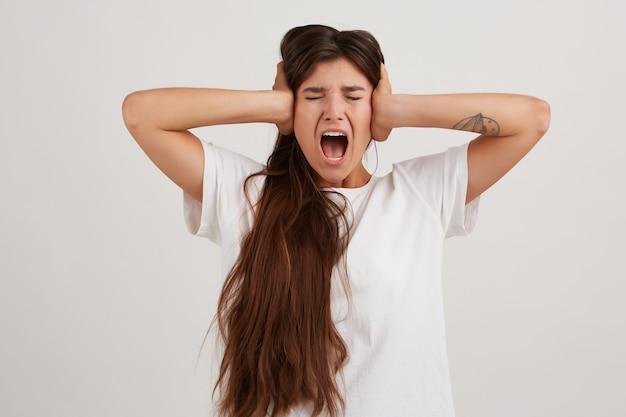 화가 난 아가씨, 흰색 티셔츠를 입고 검은 긴 머리를 가진 스트레스 여성. 문신 있음