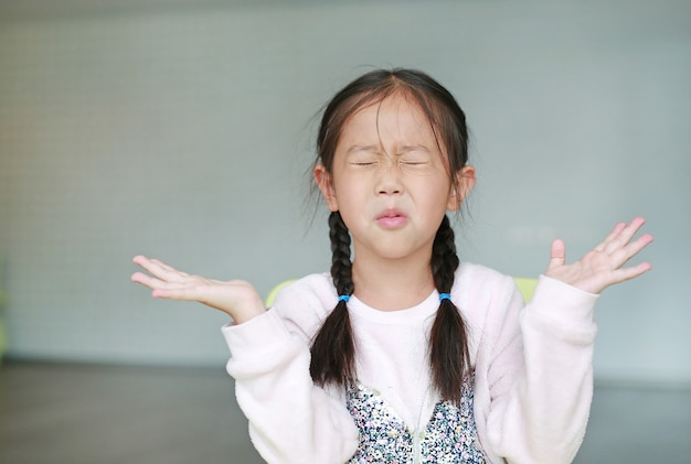 Angry little asian child girl in classroom. not listening. sign and gesture concept.