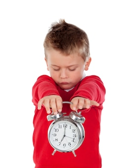 Angry little boy holding a clock