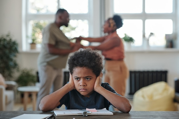 Злой маленький мальчик африканской национальности закрывает уши руками, пытаясь выполнить школьное задание против своих родителей, спорящих