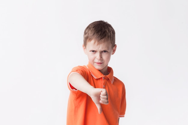 Angry little boy showing dislike gesture on white backdrop