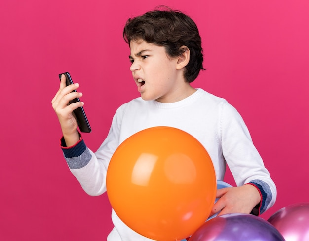Angry little boy standing behind balloons holding and looking at phone isolated on pink wall