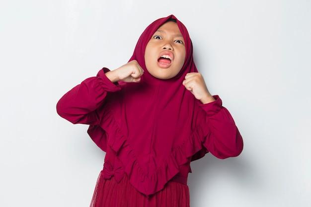 Злой маленькая милая азиатская мусульманская девушка в хиджабе изолирована на белом фоне