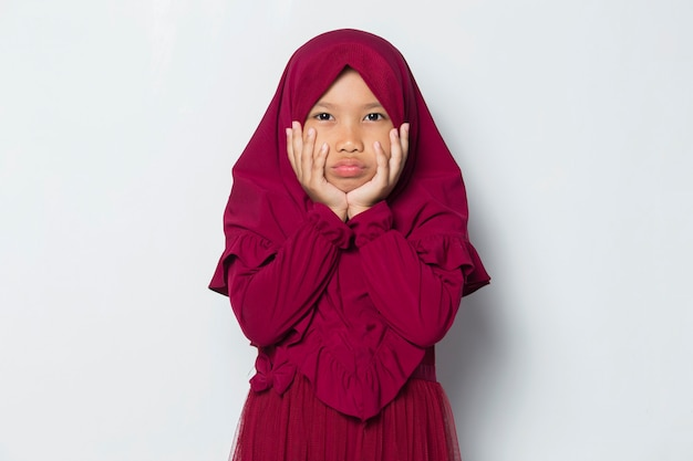 Angry little cute asian muslim hijab girl isolated on white background