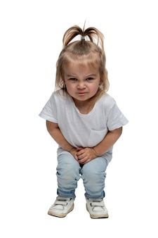 Angry little girl 2-3 years old in jeans is squatting. isolated on white background. vertical.