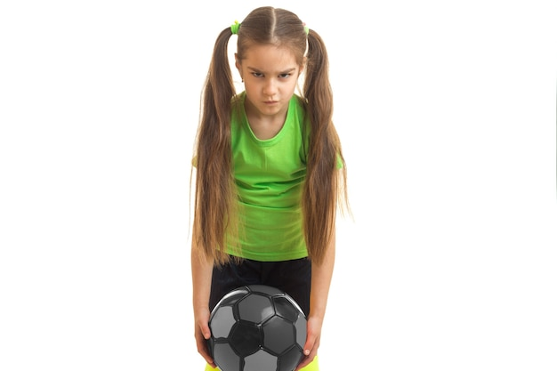 Angry little girl plays a soccer with ball isolated on white background