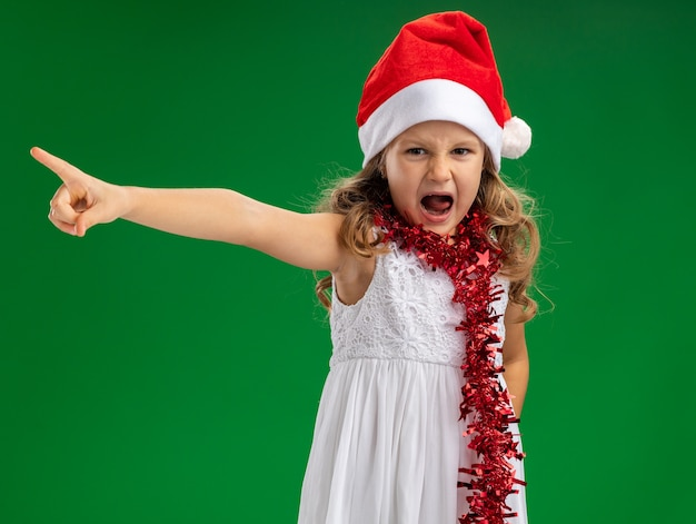 Angry little girl wearing christmas hat with garland on neck points at side isolated on green background