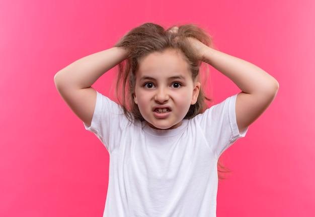 孤立したピンクの壁に白いtシャツを着て怒っている小さな女子高生が頭をつかんだ