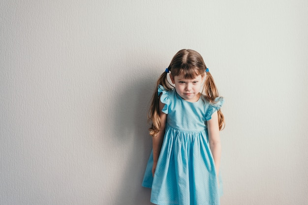 Angry little white girl in blue dress on neutral backgroung