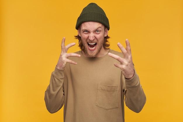 Arrabbiato cercando maschio, ragazzo barbuto scontento con i capelli biondi. indossare berretto verde e maglione beige. fa una smorfia spaventosa. isolato su muro giallo