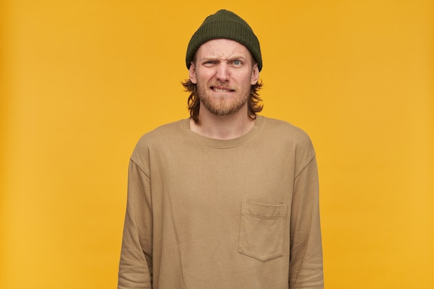 Angry looking male, frowning bearded guy with blond hairstyle. wearing green beanie and beige sweater. bites his lip.  isolated over yellow wall