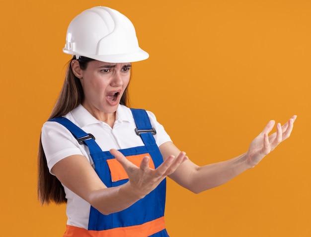 Arrabbiato guardando lato giovane costruttore donna in uniforme tendendo le mani a lato isolato sulla parete arancione