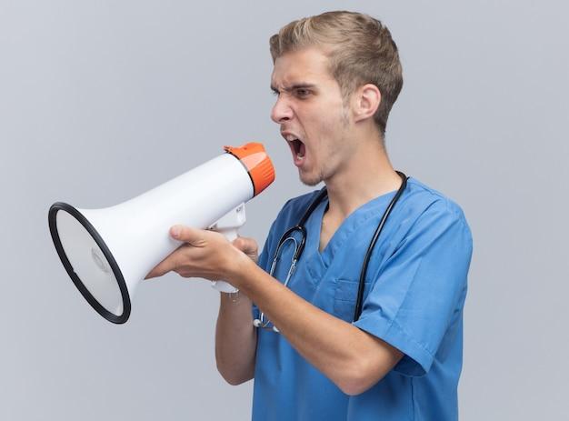 Arrabbiato guardando al lato giovane medico maschio che indossa l'uniforme del medico con lo stetoscopio parla sull'altoparlante isolato sul muro bianco