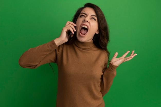 Злой глядя вверх молодая красивая девушка разговаривает по телефону и протягивает руку, изолированную на зеленой стене