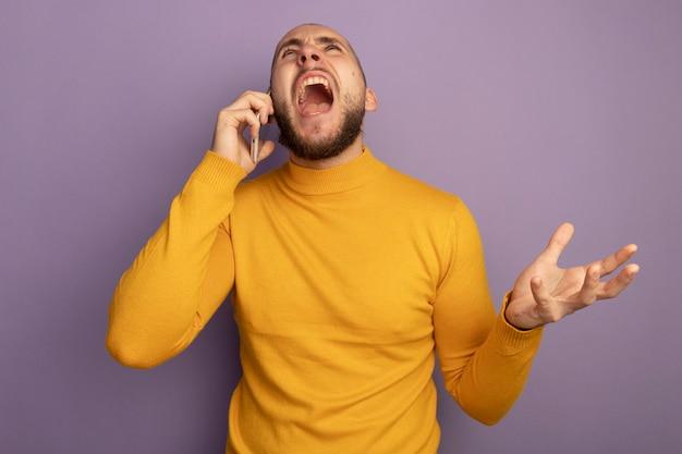Злой глядя вверх молодой красивый парень говорит по телефону, протягивая руку, изолированную на фиолетовой стене