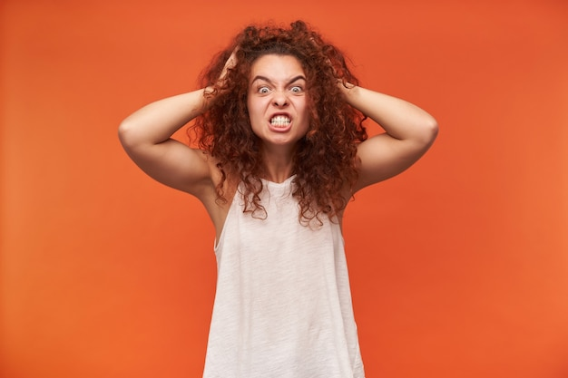 Angry looking woman, crazy girl with curly ginger hair. wearing white off-shoulder blouse. touching her head, terrible headache. isolated over orange wall