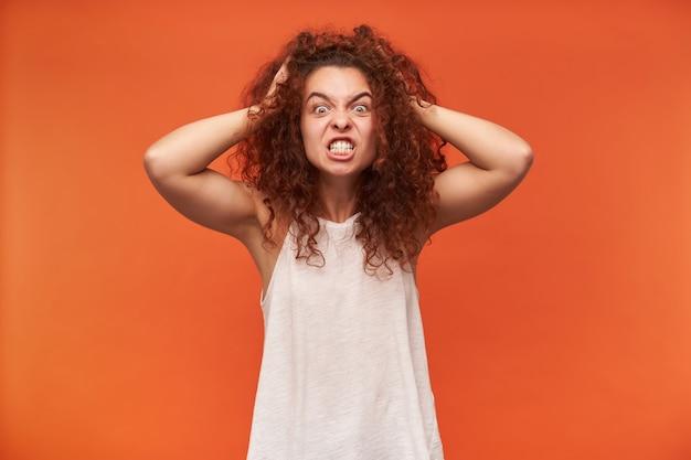 Donna dall'aspetto arrabbiato, ragazza pazza con i capelli ricci di zenzero. indossare camicetta bianca con spalle scoperte. toccandole la testa, un terribile mal di testa. isolato sopra il muro arancione