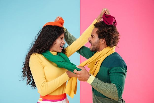 立って議論している帽子とスカーフで怒っている狂ったアフリカのカップル
