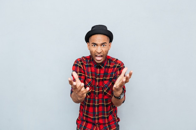 Angry mad african man in plaid shirt standing and shouting