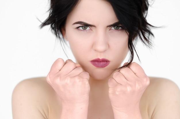 Сердитый безумный крест женщина сжимая кулаки на белой стене.