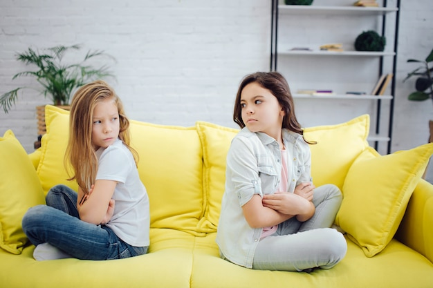 Angry and mad girls sit on yellow sofa in room. girls are very upset.