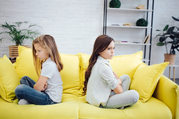 Angry and mad girls sit on yellow sofa in room. they don't look at each other. girls are very upset.